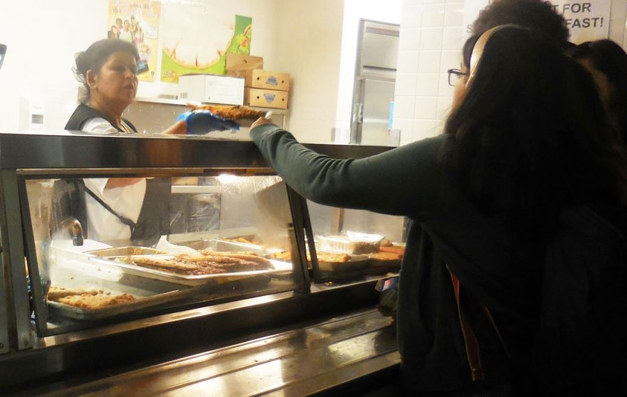 One of the cafeteria staff serving the lunch to the students.