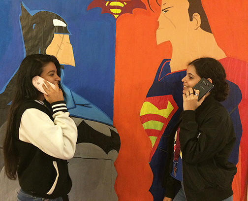 Sophomore Keylene Cortez discussing with sophomore Yeraldine Ruiz about which phone is better.