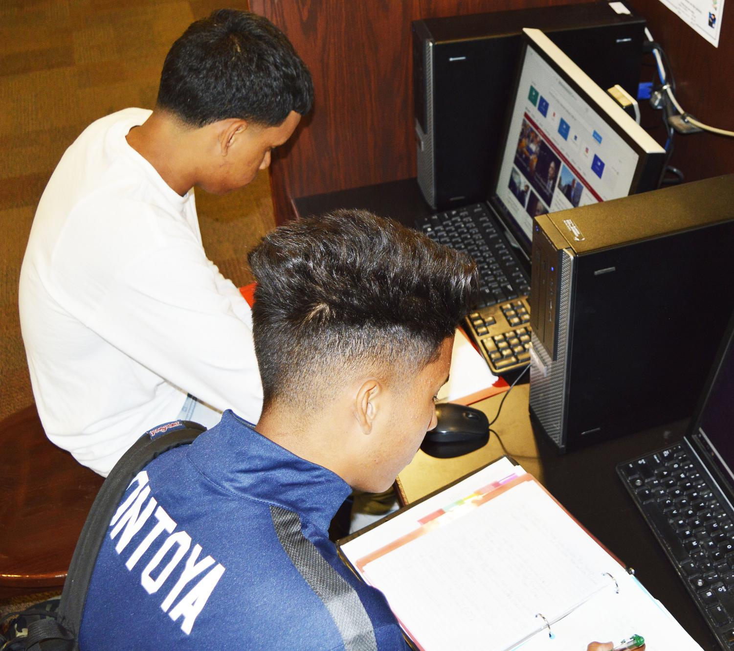 Soccer players Franklin Montoya (right) and Rafael Zuniga (left) putting time aside to study.