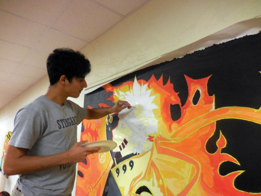 Senior+Rolando+Herrera+adds+the+finishing+touches+to+his+vibrant+orange-and-black+painting+of+Naruto