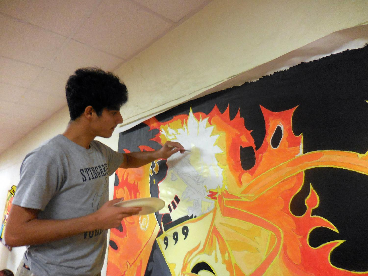 Senior Rolando Herrera adds the finishing touches to his vibrant orange-and-black painting of Naruto