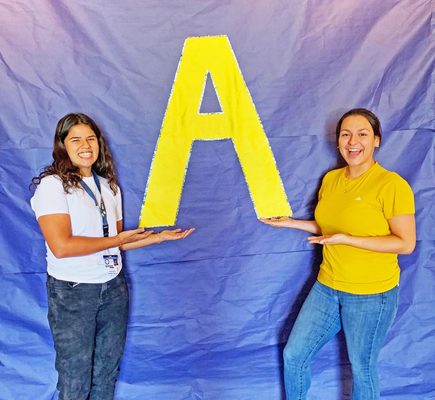 Victoria Millon (left) and Samantha Garcia (Right ) posing in front of poster