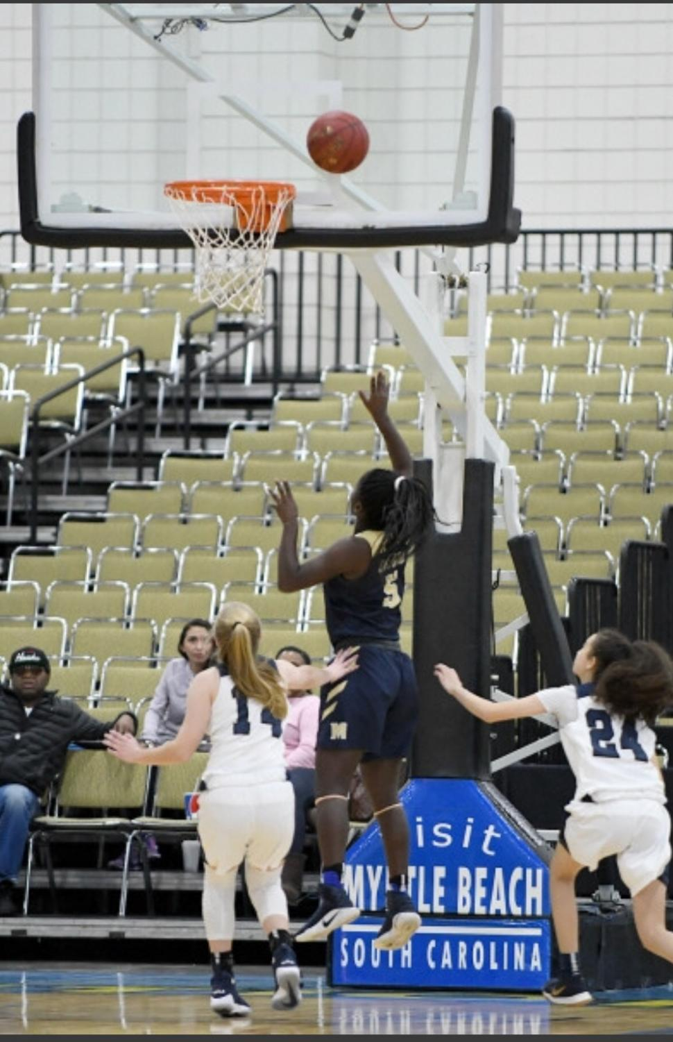 12th grader Darriah Whitley, center, playing her favorite sport, basketball.