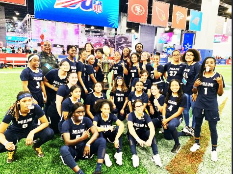 Girls flag football team posing with their trophy after winning the Nike Combine at the Miami Beach Convention Center.